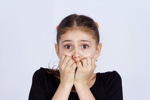 Przestraszona dziewczynka obgryzająca paznokcie
