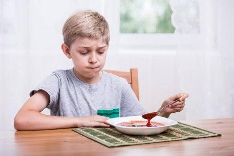 Skrzywiony chłopiec grzebiący łyżką w zupie
