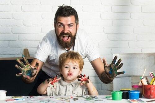 Śmiejący się tata i syn z rękoma umazanymi farbą, malujący obrazki