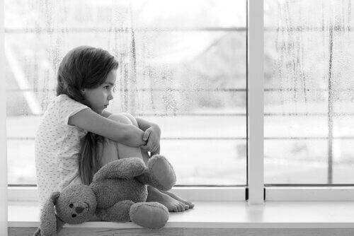 Smutna dziewczynka siedząca skulona na parapecie