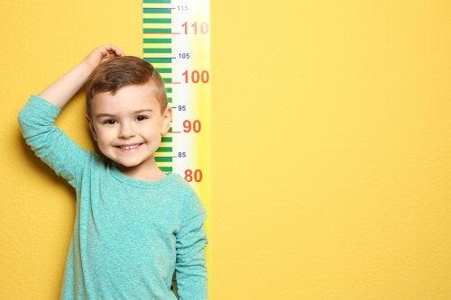 Uśmiechnięty chłopiec stojący przy miarce na ścianie - rozwój chłopca