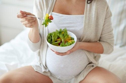Kobieta w ciąży jedząca sałatkę