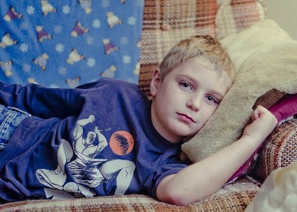 Chłopiec leżący na boku na kanapie