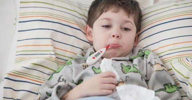 Chłopiec leżący w łóżku z termometrem w ustach - przeziębienie u dziecka