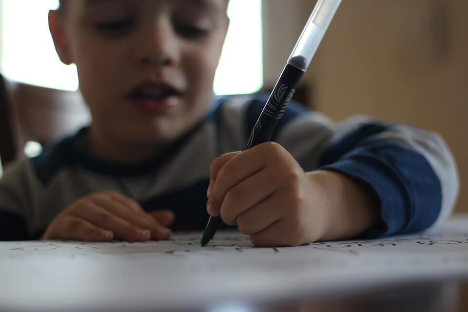 Chłopiec piszący na kartce