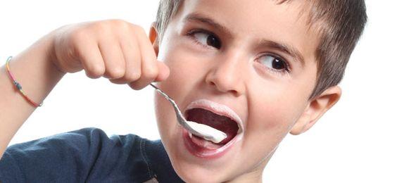 Chłopiec wkładający do ust łyżeczkę z jogurtem