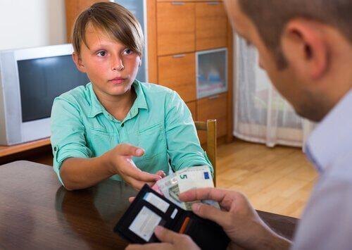 Chłopiec wyciągający do taty rękę po pieniądze - jak nauczyć dziecko wartości pieniądza?