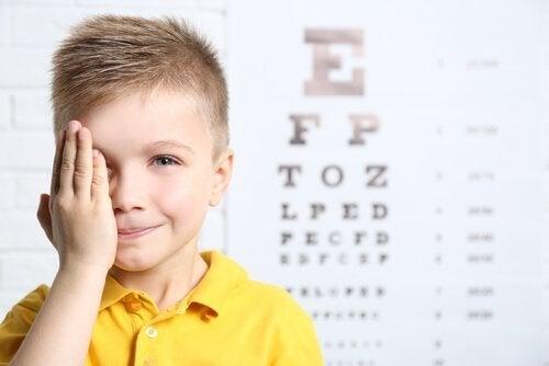 Chłopiec zasłaniający jedno oko dłonią