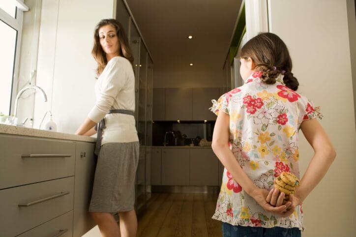 Dziewczynka chowająca za plecami ciastka przed mama
