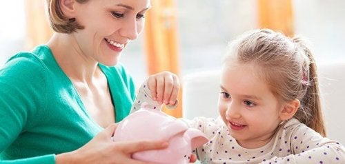Dziewczynka wrzucająca monetę do skarbonki trzymanej przez mamę