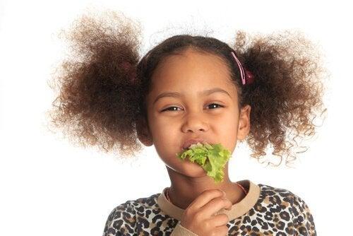 Dziewczynka z liściem sałaty w ustach - witaminy na jesień