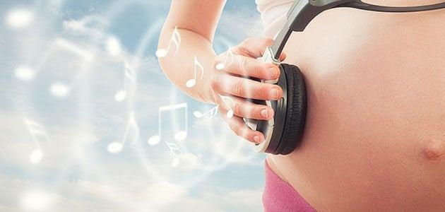 Kobieta przykładająca słuchawkę do brzucha w ciąży - stymulacja prenatalna