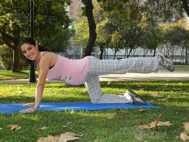 Kobieta w ciąży ćwicząca na macie na zewnątrz