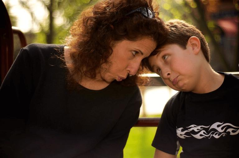 Mama i syn z ustami wygiętymi w podkówkę, dotykający się czołami