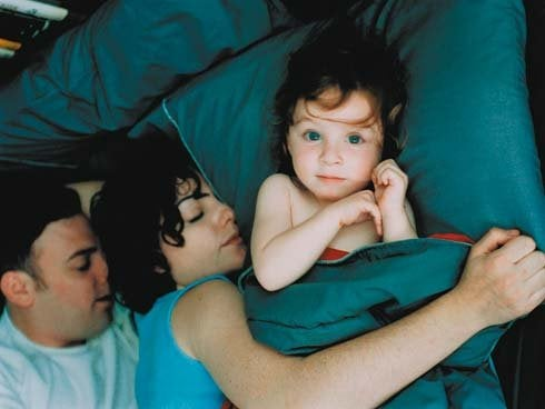 Mama i tata leżący w łóżku z dzieckiem - problemy ze snem