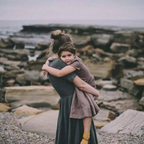 Mama trzyma w ramionach córkę