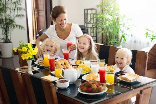 Mama z trójką dzieci przy stole podczas śniadania