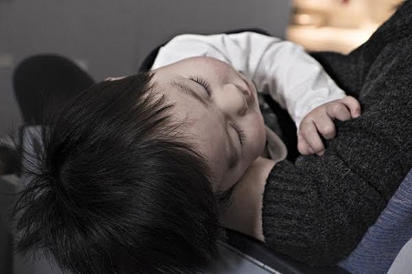 Niemowlę śpiące na kolanach mamy