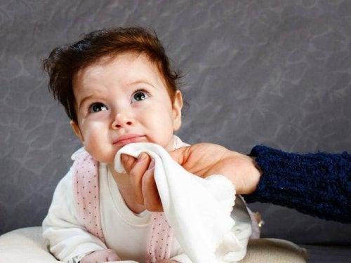 Ręka wycierająca chusteczką brodę dziecka - choroba refluksowa przełyku
