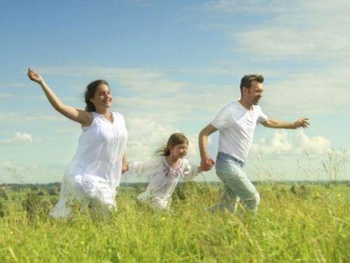 Szczęśliwa rodzina w białych strojach biegnie po łące