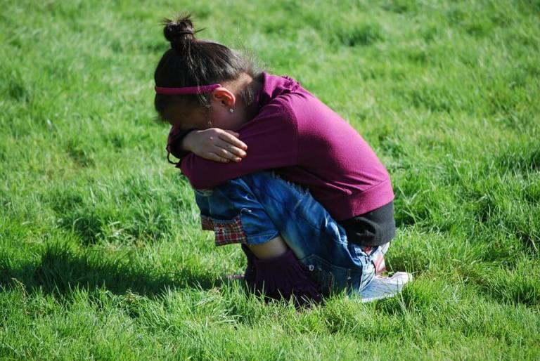 Skulona dziewczynka na trawniku - dziecko jest nieśmiałe