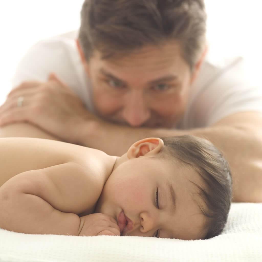 Tata patrzący na śpiące niemowlę