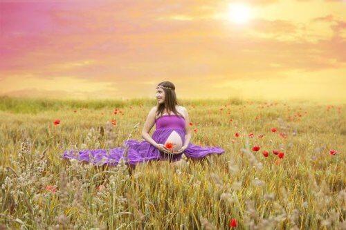 Uśmiechnięta kobieta w ciąży na polu - świadoma ciąża