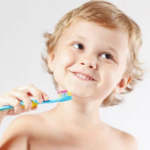 Uśmiechnięty chłopiec trzymający szczoteczkę do zębów - jak wyrobić dobre nawyki w dziecku