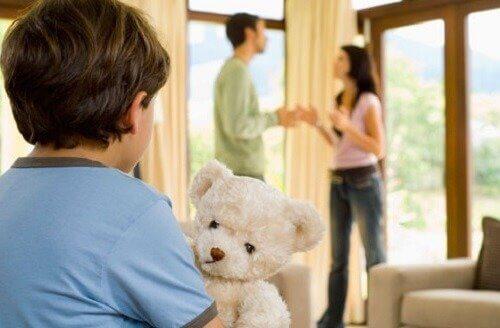 Chłopiec z misiem patrzący na kłócących się rodziców