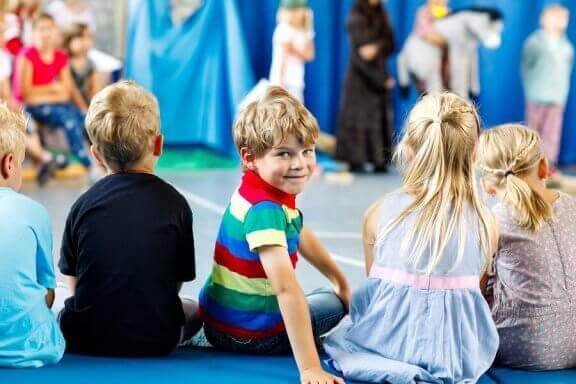 Dzieci siedzące na podłodze i oglądające przedstawienie - wyrażanie emocji poprzez teatr