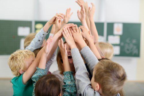 Dzieci w kółku podnoszące ręce do góry - kontekst szkolny