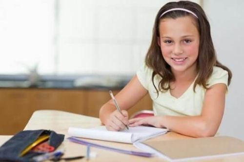 Dziewczyna uczy się przy biurku