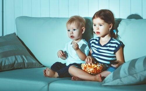 Dziewczynka i chłopiec oglądający telewizję i jedzący popcorn
