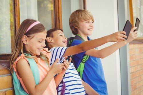 Dziewczynka i dwóch chłopców robiących selfie