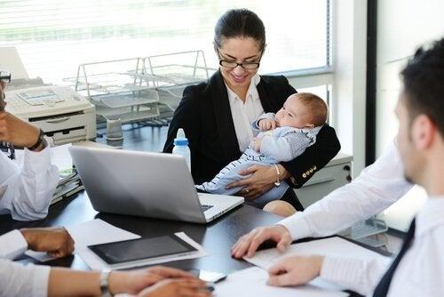 Kobieta na spotkaniu w pracy z dzieckiem - powrót do pracy po urlopie macierzyńskim