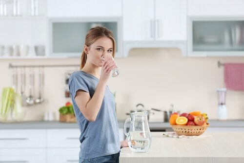 Kobieta pijąca wodę ze szklanki - zadbaj o nawilżenie skóry