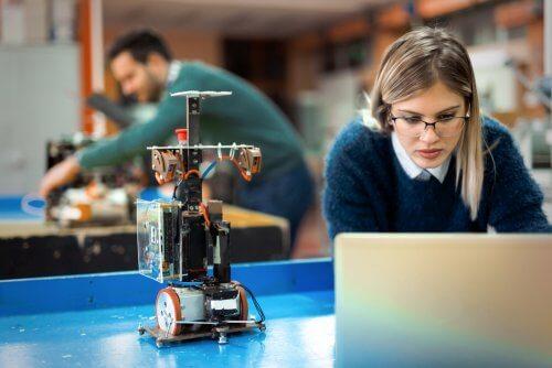 Kobieta wpatrzona w laptop stojący obok mikroskopu