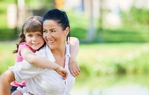 Mama nosząca córkę na plecach