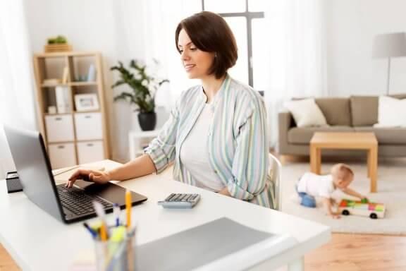 Mama siedząca przy laptopie, w tle bawiące się dziecko