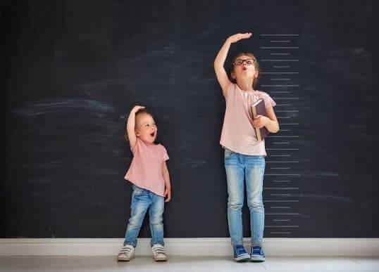 Młodsza i starsza siostra mierzące wzrost - kolejność narodzin