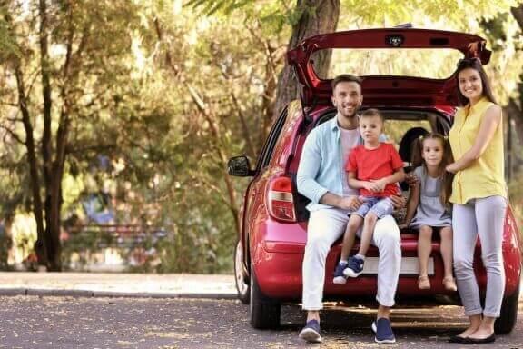 Rodzina siedząca w otwartym bagażniku samochodu - minivany dla dużej rodziny