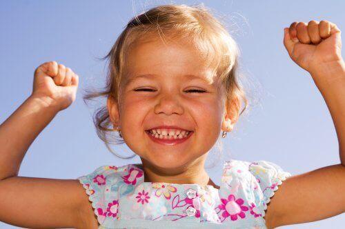 Szczęśliwa dziewczynka unosząca ręce do góry - jak obudzić w dziecku optymizm?
