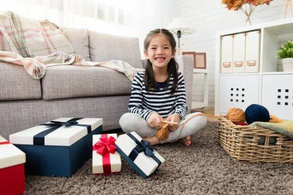 Uśmiechnieta dziewczynka siedząca na podłodze, otoczona prezentami