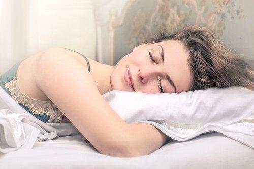 Uśmiechnięta kobieta śpiąca w łóżku