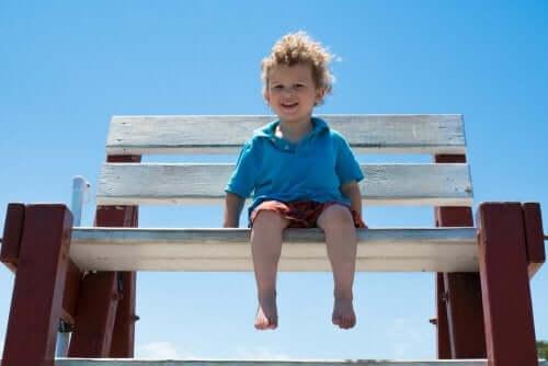 Bosy chłopiec na ławce na plaży - jak dbać o stopy dziecka