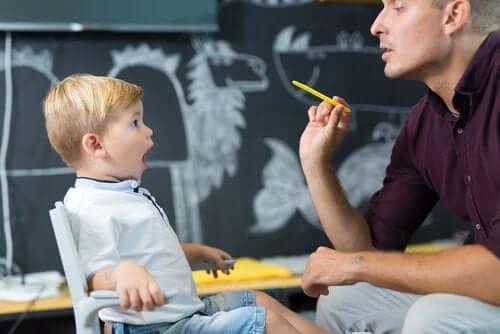 Chłopiec ćwiczący z logopedą - akwizycja języka u dzieci