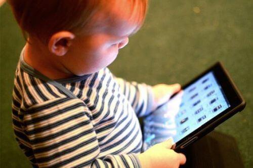 Dziecko siedzi z tabletem, który czasami może opóźniać rozwój mowy
