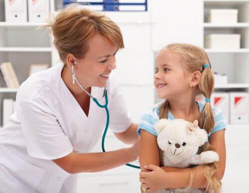 Lekarka badająca dziewczynkę przytulającą misia