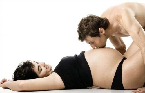 Mężczyzna całuje ciężarną kobietę w brzuch