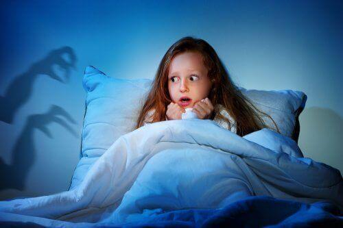 Przerażona dziewczynka w łóżku bojąca się ciemności - lęki u dzieci